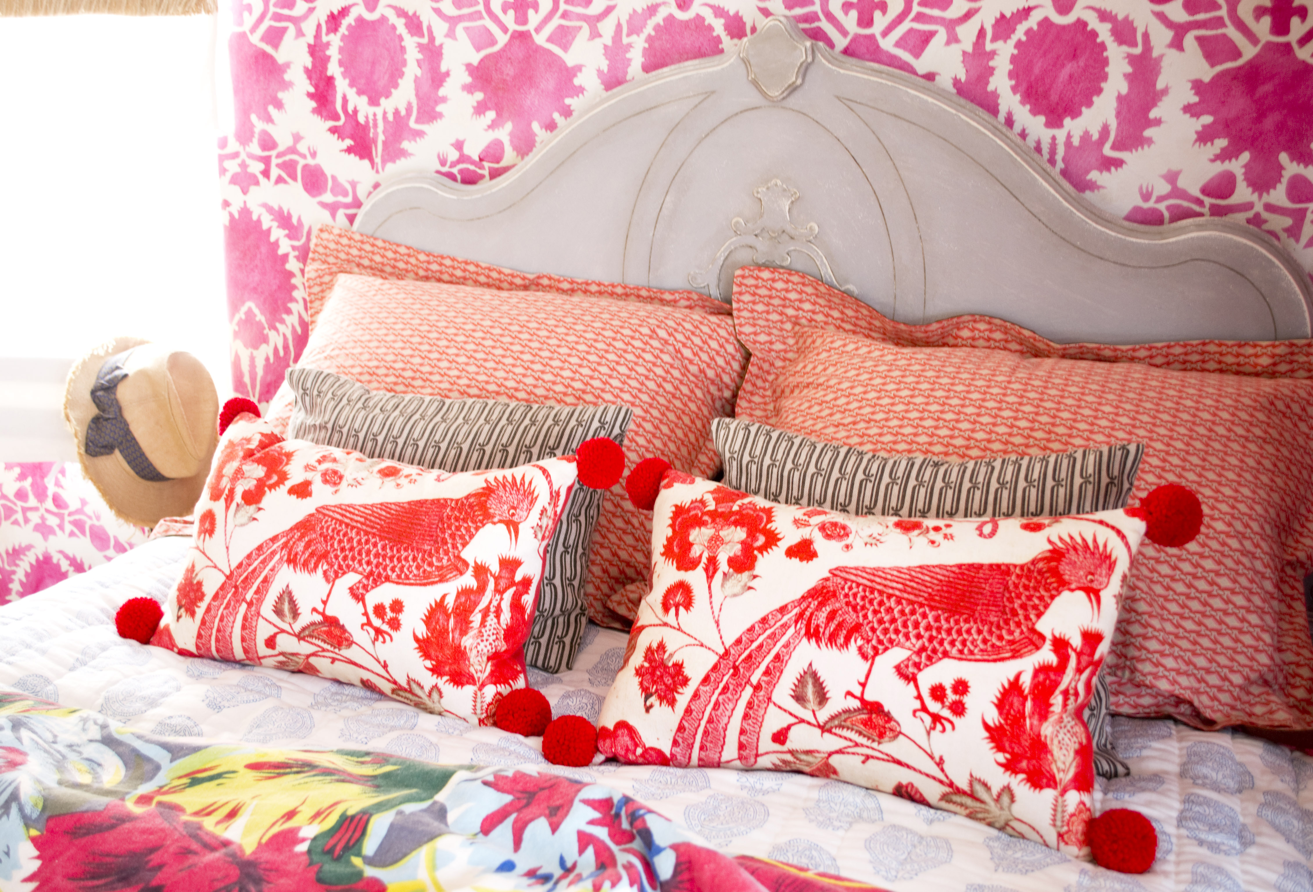 Red Pom Pom Pillow on Bed